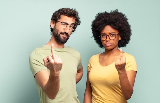 Gemischtrassiges freundespaar, das wütend, verärgert, rebellisch und aggressiv ist, den mittelfinger zeigt und sich wehrt
