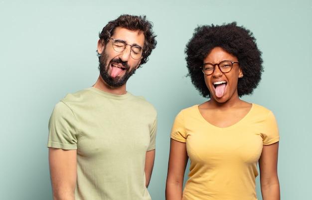 Gemischtrassiges freundespaar mit fröhlicher, sorgloser, rebellischer einstellung, scherzen und herausstreckender zunge, spaß haben