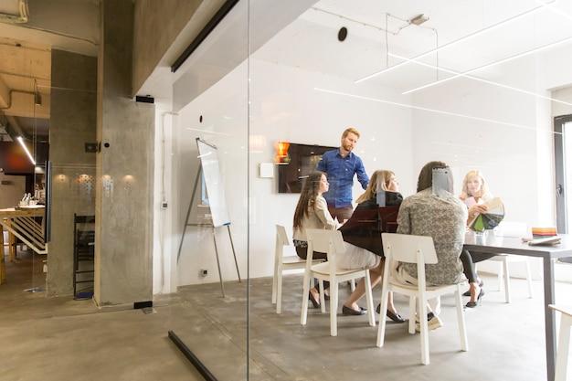 Gemischtrassiges modernes geschäftsteam, welches die strategie des unternehmens im büro entwickelt