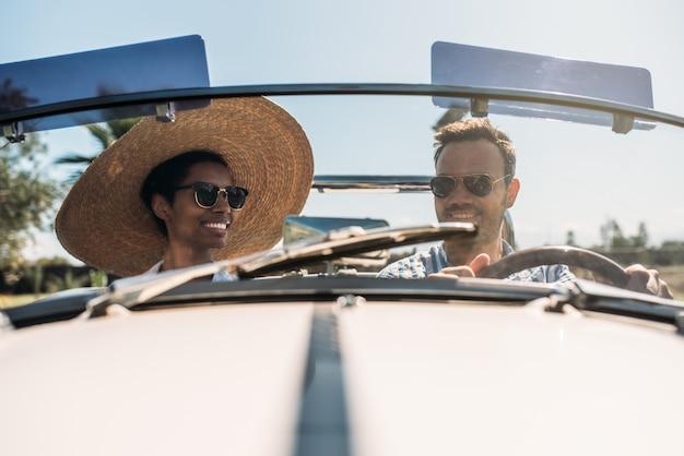 Gemischtrassiges paar in einem cabrio-oldtimer