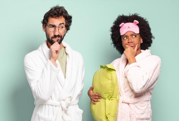 Gemischtrassiges paar von freunden, die denken, sich zweifelnd und verwirrt fühlen, mit verschiedenen optionen, sich fragen, welche entscheidung sie treffen sollen. pyjamas und wohnkonzept