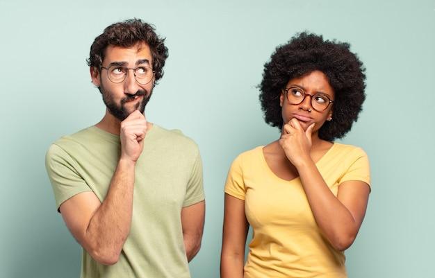 Gemischtrassiges paar von freunden, die denken, sich zweifelnd und verwirrt fühlen, mit verschiedenen optionen, sich fragen, welche entscheidung sie treffen sollen