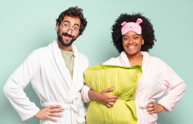 Gemischtrassiges paar von freunden, die glücklich mit einer hand auf hüfte lächeln und selbstbewusste, positive, stolze und freundliche haltung. pyjama und heimkonzept