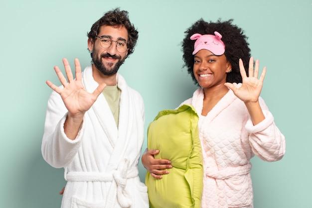 Gemischtrassiges paar von freunden, die lächeln und freundlich aussehen, die nummer fünf oder fünf mit der hand nach vorne zeigen, herunterzählen. pyjamas und wohnkonzept