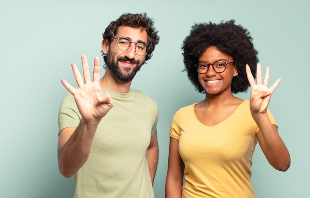 Gemischtrassiges paar von freunden, die lächeln und freundlich aussehen, die nummer vier oder vier mit der hand nach vorne zeigen