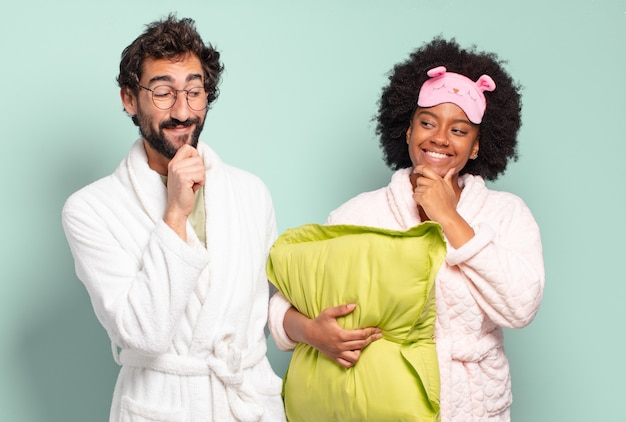 Gemischtrassiges paar von freunden, die mit einem glücklichen, selbstbewussten ausdruck mit der hand am kinn lächeln, sich wundern und zur seite schauen. pyjama und heimkonzept