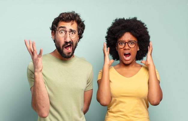 Gemischtrassiges paar von freunden, die mit erhobenen händen schreien und sich wütend, frustriert, gestresst und verärgert fühlen