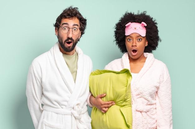 Gemischtrassiges paar von freunden, die sehr schockiert oder überrascht aussehen und mit offenem mund anstarren und sagen, wow. pyjamas und wohnkonzept