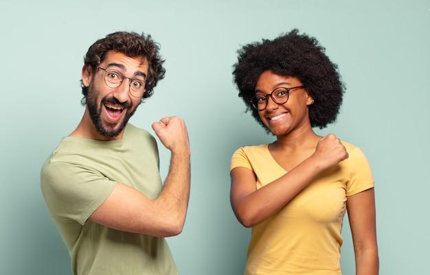 Gemischtrassiges paar von freunden, die sich glücklich, positiv und erfolgreich fühlen, motiviert sind, wenn sie sich einer herausforderung stellen oder gute ergebnisse feiern
