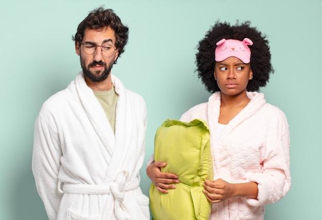 Gemischtrassiges paar von freunden, die sich traurig, verärgert oder wütend fühlen und mit einer negativen einstellung zur seite schauen und die stirn runzeln. pyjamas und wohnkonzept