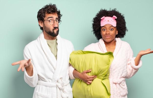 Gemischtrassiges paar von freunden, die sich verwirrt und verwirrt fühlen, zweifeln, gewichten oder verschiedene optionen mit lustigem ausdruck wählen. pyjamas und wohnkonzept