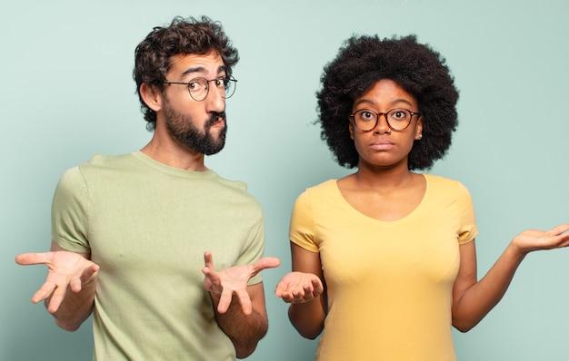 Gemischtrassiges paar von freunden, die sich verwirrt und verwirrt fühlen, zweifeln, gewichten oder verschiedene optionen mit lustigem ausdruck wählen