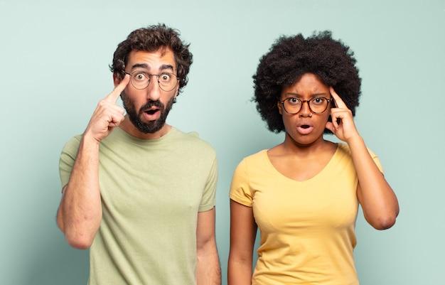 Gemischtrassiges paar von freunden, die überrascht, mit offenem mund, schockiert aussehen und einen neuen gedanken, eine neue idee oder ein neues konzept verwirklichen