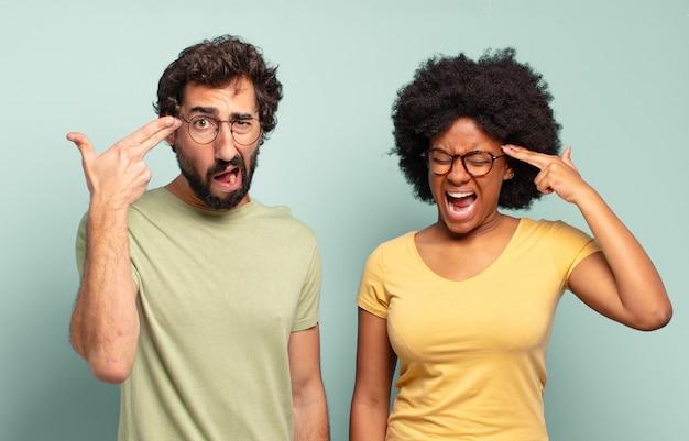 Gemischtrassiges paar von freunden, die unglücklich und gestresst aussehen, selbstmordgeste, die mit der hand ein waffenschild macht und auf den kopf zeigt
