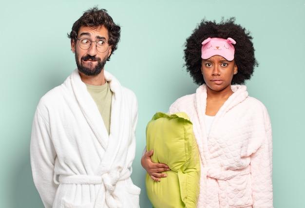 Gemischtrassiges paar von freunden, die verwirrt und verwirrt aussehen, sich mit einer nervösen geste auf die lippe beißen und die antwort auf das problem nicht kennen. pyjamas und wohnkonzept