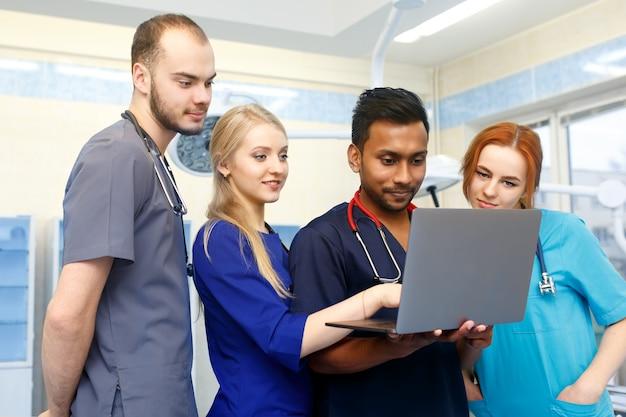 Gemischtrassiges team junger doktoren, die an laptop-computer im ärztlichen dienst arbeiten.