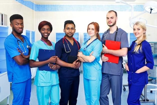Gemischtrassiges team junger doktoren in einem krankenhaus, das in einem operationsraum steht