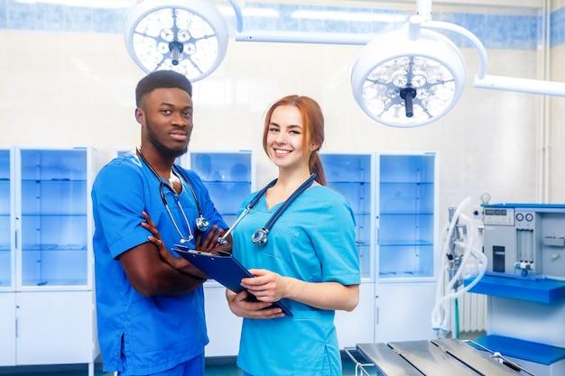 Gemischtrassiges team von zwei jungen doktoren in einem krankenhaus, das in einem operationsraum steht