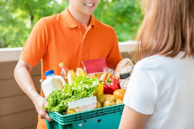 Gemischtwarenladenlieferer, der zu hause lebensmittel an eine frau liefert