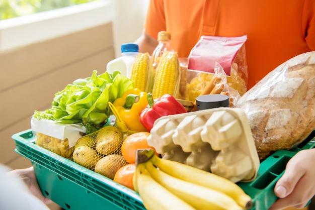 Gemischtwarenladenlieferer, der zu hause lebensmittel an einen kunden liefert