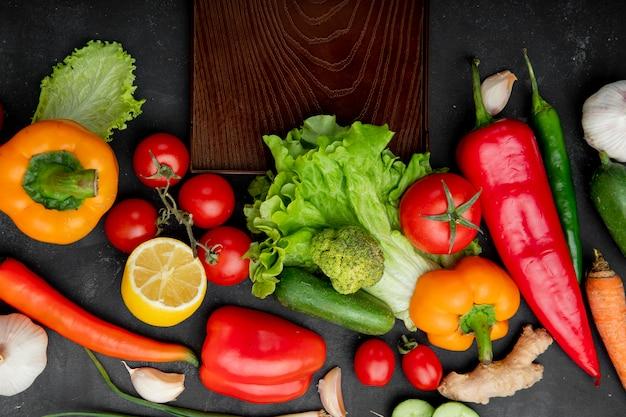 Gemüse als pfeffersalattomate und andere mit zitrone und schneidebrett auf schwarzem tisch