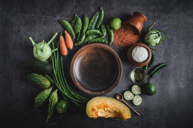 Gemüse auf einem schwarzen tisch mit platz für eine nachricht in der mitte