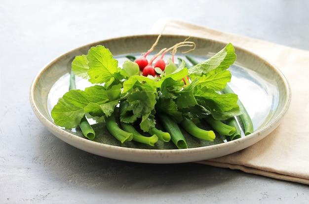 Gemüse auf einer platte, frühlingszwiebeln, rettiche auf einem grauen hintergrund.