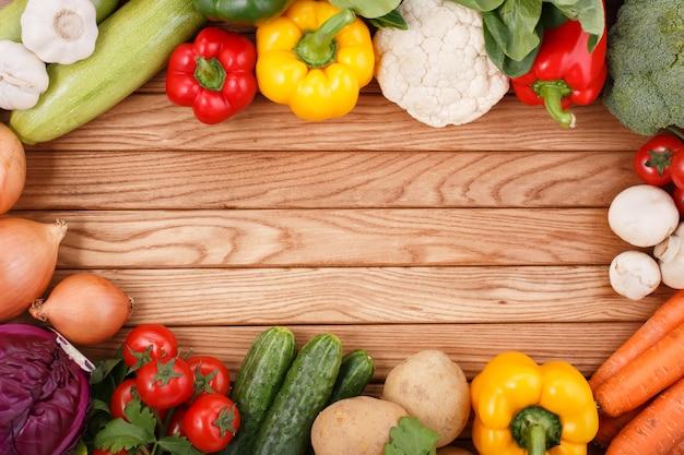 Gemüse auf hölzernem hintergrund mit platz für text.