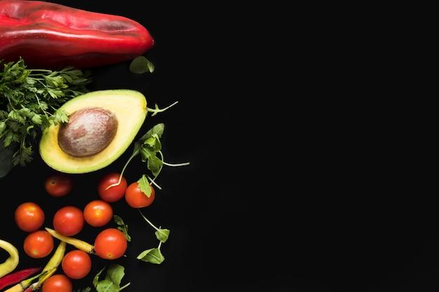 Gemüse auf schwarzem hintergrund mit kopienraum