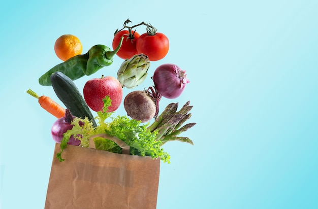 Gemüse fliegt in recycelbarer papiertüte mit kopierraum