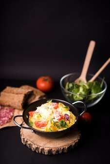 Gemüse gekochte teigwaren, wenn topf auf hölzernem untersetzer gekocht wird
