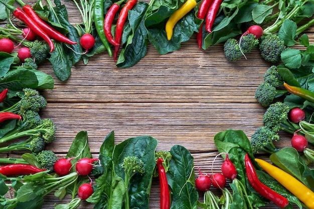 Gemüse hintergrund. rettich, brokkoli, paprikapfeffer, spinat verlässt auf altem holztisch