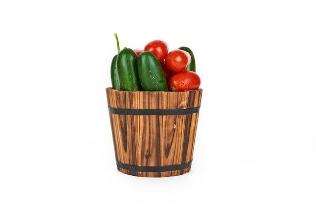 Gemüse im hölzernen eimer auf einem weißen.