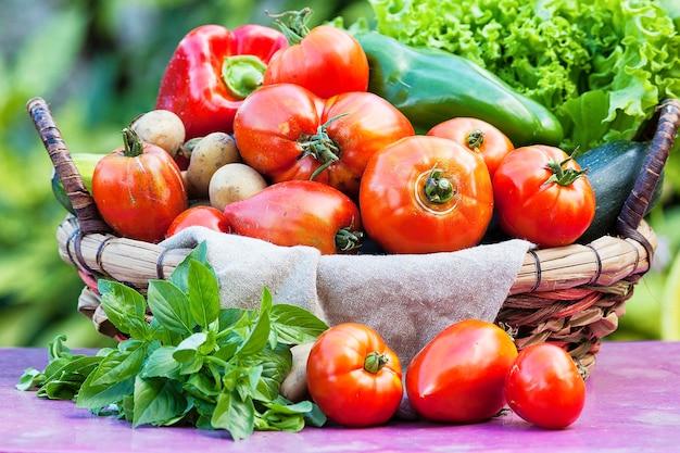 Gemüse in einem korb auf tisch unter sonnenlicht