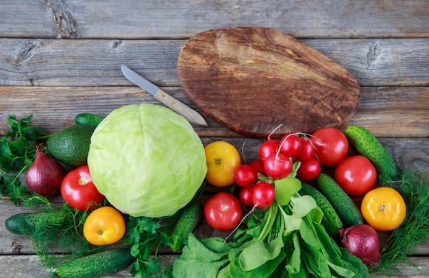Gemüse in einer reihe gelegt: kohl, zwiebeln, gurken, petersilie, dill, avocados, radieschen, tomaten und ein schneidebrett und ein messer