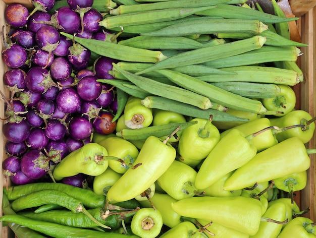 Gemüse in maiskolben in einer rustikalen holzkiste, paprika, auberginen und roselle