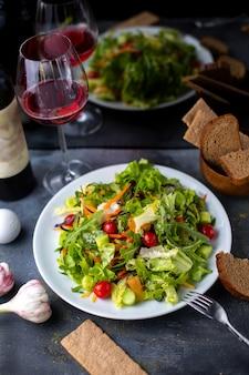 Gemüse in scheiben geschnitten zusammen mit rotwein in weißen teller