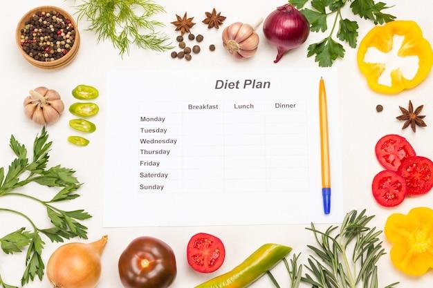 Gemüse, kräuter und gewürze sowie ein blatt papier mit diätplan für die woche