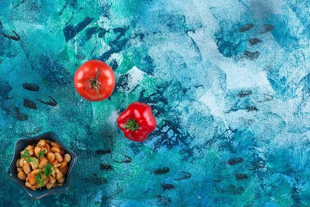 Gemüse mit einer schüssel gebackene bohnen, auf dem blauen tisch.
