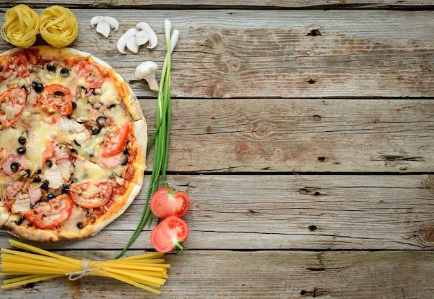 Gemüse-, pilz- und tomatenpizza auf einem hölzernen hintergrund