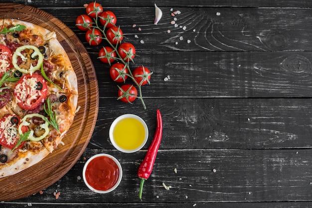 Gemüse-, pilz- und tomatenpizza auf einem schwarzen hölzernen hintergrund. es kann als hintergrund verwendet werden