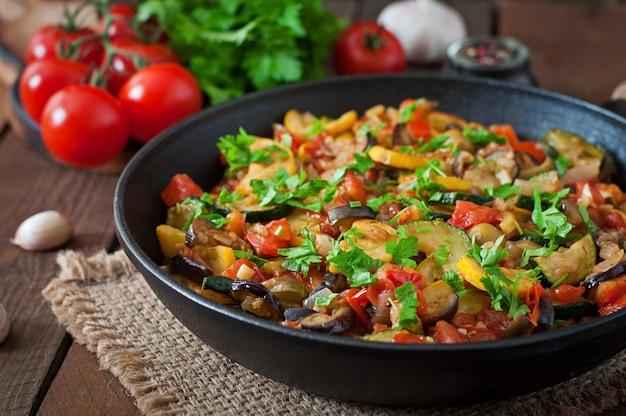 Gemüse ratatouille in der pfanne auf einem holztisch
