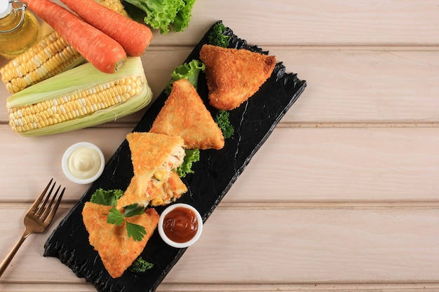 Gemüse-risole mit dreiecksform. dünne crepes gefüllt mit rogusa-mais, karotten und grünen bohnen, serviert auf schwarzem steinteller mit käse, mayonaise und chilisauce. kopieren sie platz auf holzhintergrund