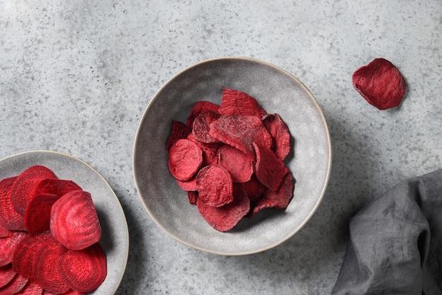 Gemüse-rote-bete-chips in grauer schüssel auf weißem hintergrund