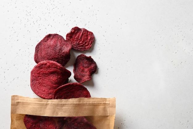 Gemüse-rote-bete-chips in papier-bastelverpackung auf weißem hintergrund