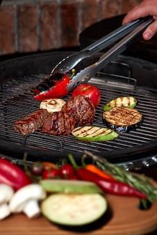Gemüse und fleisch brutzeln auf dem grill mit flammen