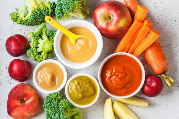 Gemüse- und fruchtbabypüree in den weißen schüsseln mit bestandteilen.
