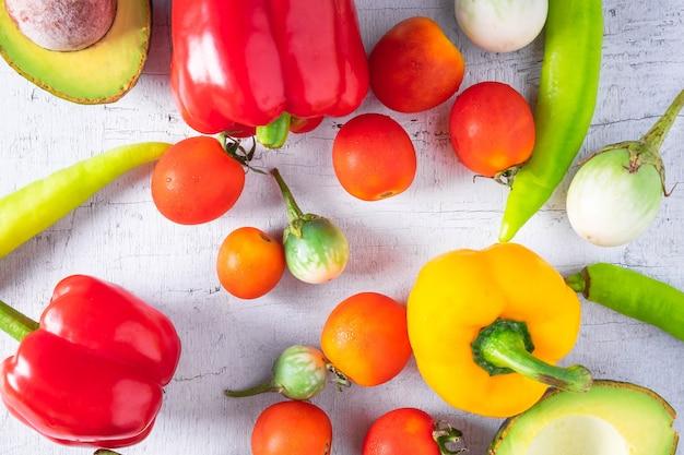 Gemüse und früchte auf einem weißen hölzernen hintergrund.