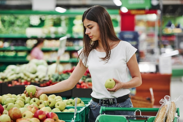 Gemüse und früchte. weibliche käuferin in freizeitkleidung auf dem markt, der nach produkten sucht.