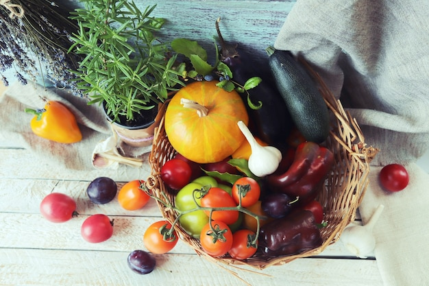 Gemüse und obst in einem korb würzige kräuter auf einem holztisch-herbst-ernte-konzept